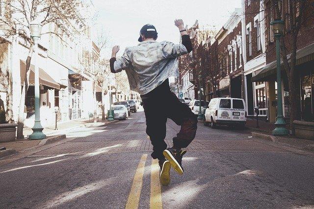 A man flying through the air while riding a skateboard down a street